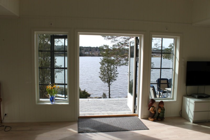 Blick aus dem Wohnzimmer auf die Terrasse am Wasser