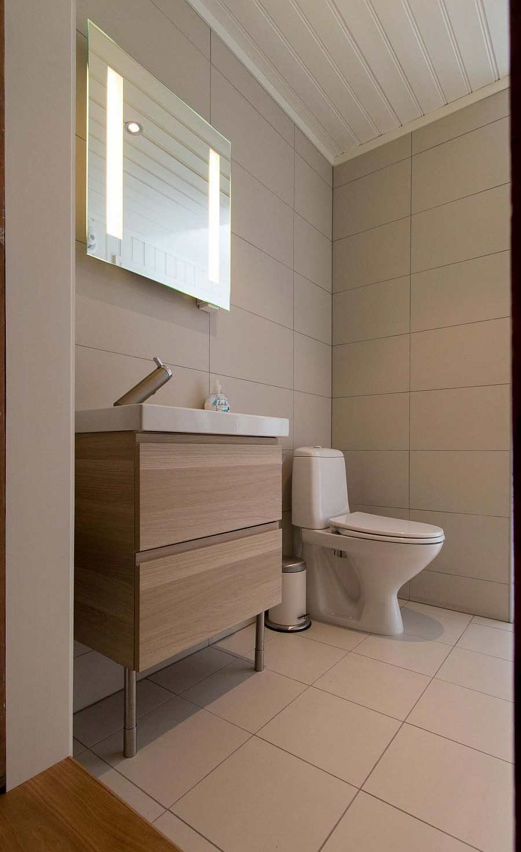 Das zweite Badezimmer im Haus mit Waschbecken, Dusche/WC und Zugang zur Sauna