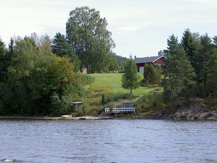 Blick vom Wasser auf das Grundstück (rechts der rote Schuppen, das Ferienhaus liegt hinter dem großen Baum)