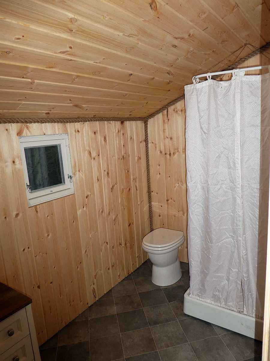Das Badezimmer des Hauses mit Waschbecken, Dusche und moderner Biotoilette