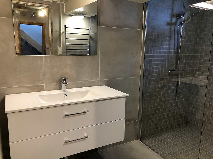 Das Badezimmer mit Dusche, Waschbecken und Fußbodenheizung