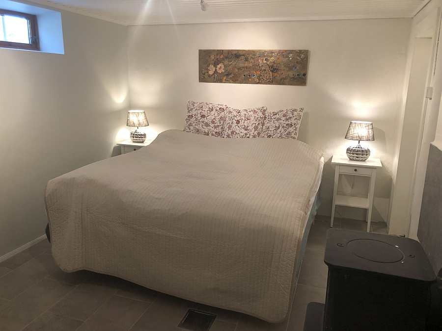 Das erste Schlafzimmer mit einem Doppelbett. Holzofen kann für die Gemütlichkeit genutzt werden.