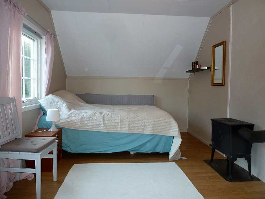 Das Schlafzimmer mit einem Doppel- und einem Einzelbett. Der Holzofen kann für die Gemütlichkeit genutzt werden.