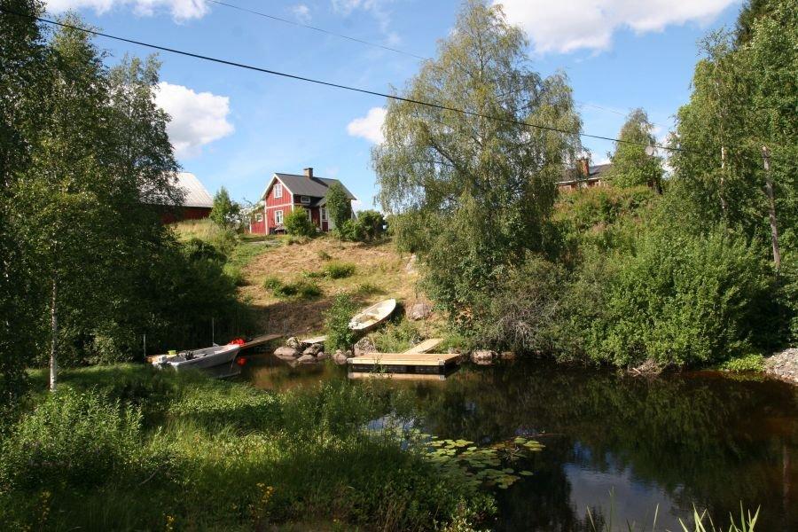 Im Vordergrund der kleine Fluss in dem das Boot liegt und dahinter Haus Norra Fors